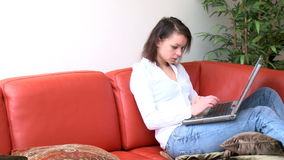 Unworried woman using a laptop. Sitting on sofa stock video footage