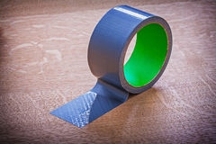Unwound duct tape on vintage wooden board. Maintenance concept stock photos