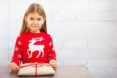 unwraping圣诞礼物的愉快的女孩 图库摄影