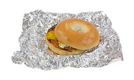 Unwrapped breakfast bagel sandwich on tinfoil Royalty Free Stock Photos