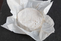 Unwrapped English Brie soft cheese on a grey slate background. Wrapped English Brie soft cheese on a grey slate background Stock Image
