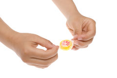 Unwrapping a candy. With hands on white background Royalty Free Stock Images