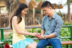 Unwrapping gift box. Young Vietnamese couple unwrapping gift box together Royalty Free Stock Image