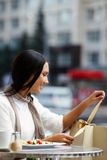 Unwrapping paperbag. Image of happy female in open air cafe unwrapping ribbon of paperbag in urban environment Stock Photos
