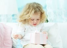 Unwrapping present. Close-up of a cute girl unwrapping her birthday present Royalty Free Stock Photo