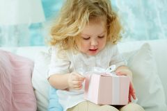 Unwrapping present. Close-up of a cute girl unwrapping her birthday present Stock Image