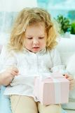 Unwrapping present. Close-up of a cute girl unwrapping her birthday present Royalty Free Stock Images
