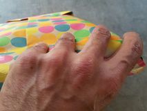 Unwrapping a present. Mans hands holding or unwrapping a colorful present Royalty Free Stock Image
