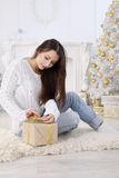 Unwraps a gift Stock Photography