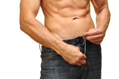 Unzip jeans. Sexy man with lean abdominals unzips his jeans on white background Royalty Free Stock Image