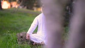 Uomini in abbigliamento bianco che fa meditazione nel parco stock footage