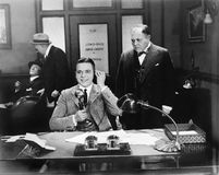 Uomini ad un ufficio uno sul telefono (tutte le persone rappresentate non sono vivente più lungo e nessuna proprietà esiste Garan Immagini Stock Libere da Diritti