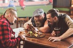 Uomini adulti che mangiano alimento non sano in pub Fotografia Stock