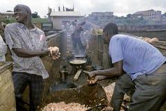 Uomini africani che riscaldano le budella del pesce per lubrificare, Kampala Fotografie Stock Libere da Diritti