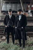 Uomini alla moda dei gangster, posanti sul fondo della ferrovia tema dell'Inghilterra nel 1920 s gruppo sicuro brutale alla moda  Fotografia Stock Libera da Diritti
