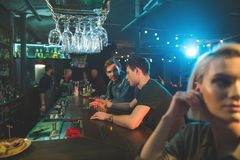 Uomini allegri che bevono i cocktail al contatore della barra Immagine Stock Libera da Diritti