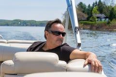 Uomini 60 anni che si rilassano su una barca Fotografie Stock