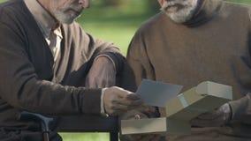 Uomini anziani che ricordano gioventù esaminare le foto dall'esercito, amicizia della vita archivi video