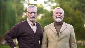 Uomini anziani eleganti che guardano macchina fotografica e pensionamento, successo e ricchezza sorridenti e felici immagine stock