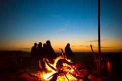 Uomini arabi che pregano Ishaa nel deserto accanto ad un posto del fuoco Fotografia Stock