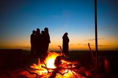 Uomini arabi che pregano Ishaa nel desrt accanto ad un posto del fuoco Immagine Stock