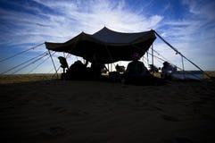 Uomini arabi che si siedono sotto una tenda nel deserto Fotografia Stock
