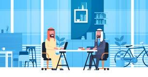 Uomini arabi di affari che si siedono alla scrivania nello spazio moderno di Coworking che lavora insieme i lavoratori musulmani  Fotografie Stock