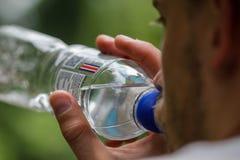 Uomini assetati con un'acqua potabile della barba da una chiara bottiglia di plastica Immagine Stock