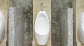 Uomini bianchi dell'orinale nella toilette pubblica degli uomini con stile del sottotetto del muro di cemento Fotografia Stock Libera da Diritti