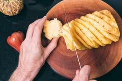 Uomini che affettano su un ananas Fotografie Stock Libere da Diritti