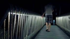 Uomini che camminano sopra il ponte di legno acceso video d archivio