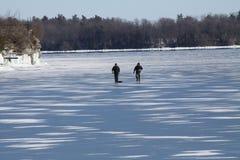 Uomini che camminano sul lago ghiacciato Fotografia Stock