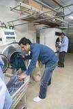 Uomini che caricano i vestiti in lavatrice alla lavanderia Fotografia Stock