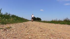 Uomini che corrono sulla strada rurale stock footage