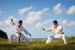 Uomini che danno dei calci al combattimento di perforazione durante il karatè Simulat di sport di combattimento Immagine Stock Libera da Diritti