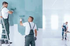 Uomini che dipingono interno domestico vuoto immagini stock