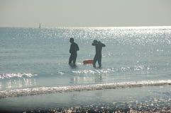 Uomini che entrano in un mare argentato e calmo fotografia stock