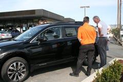 Uomini che esaminano un'automobile da vendere Fotografia Stock Libera da Diritti