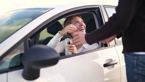 Uomini che forniscono le chiavi alla donna che si siede dentro l'automobile archivi video