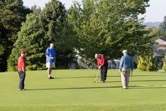 Uomini che giocano golf sul corso Immagini Stock