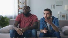 Uomini che guardano avvenimento sportivo sulla TV, esprimendo alta aspettativa e delusione video d archivio