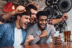 Uomini che guardano calcio sullo smartphone nella barra immagini stock