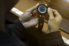 Uomini che guardano e che fissano periodo degli orologi che sono indossati nelle mani immagini stock libere da diritti