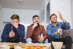Uomini che guardano insieme sport su perdita della TV a casa Fotografia Stock