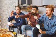 Uomini che guardano insieme sport sui fan attivi della TV a casa immagini stock