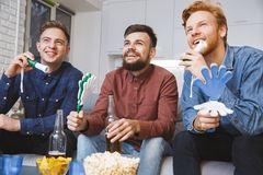 Uomini che guardano insieme sport sull'ingranaggio di spirito di gruppo della TV a casa Immagini Stock