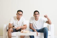 Uomini che guardano partita di football americano sulla TV a casa Fotografie Stock Libere da Diritti