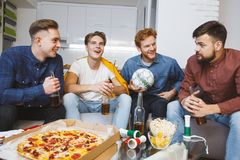 Uomini che guardano sport sulla TV a casa che discute insieme gioco fotografie stock libere da diritti