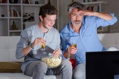 Uomini che guardano sulla televisione Immagini Stock Libere da Diritti