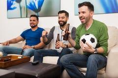 Uomini che guardano un gioco di calcio sulla TV Fotografia Stock Libera da Diritti